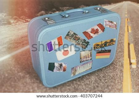 Suitcase Luggage Travel Road. Classic suitcase luggage on a surreal desert road, symbolic of travel, exploration. - stock photo