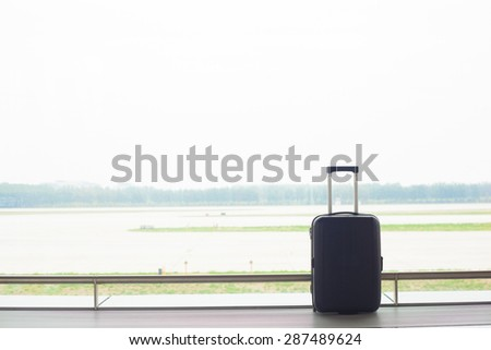 suitcase near window in an airport - stock photo
