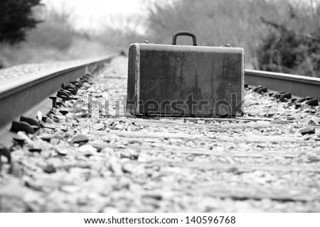 Suitcase On Railroad Tracks - This is a high contrast black and white photo of an old retro suitcase sitting on a set of railroad tracks. - stock photo