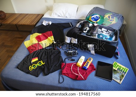 Suitcase packed for football referee trip to Brazil including red and yellow flags, whistle, camera, sunscreen, and guidebook - stock photo