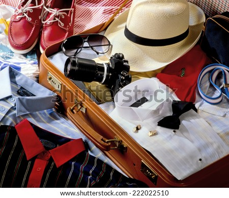 SUITCASE PACKED WITH CLOTHES - stock photo