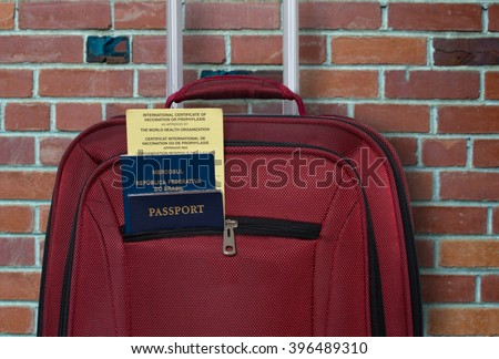 """Suitcase, two passports and Certificate of Vaccination . French text in the yellow card is a translation of English text above it. The foreign passport reads """"Mercosul- Federal Republic of Brazil"""". - stock photo"""