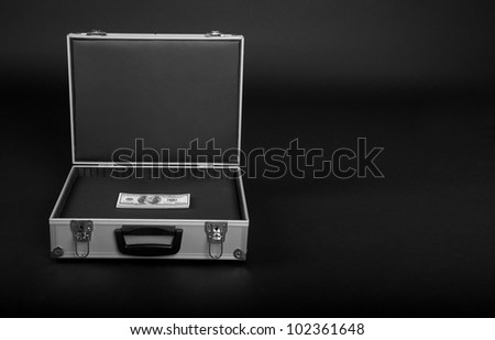 suitcase with a bunch of money on a black background - stock photo