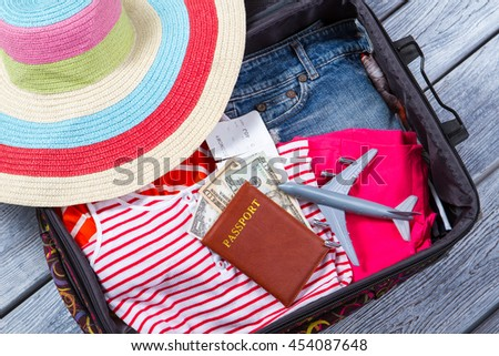 Suitcase with clothes and passport. Toy plane and beach hat. Luggage on wooden shelf. Airplane ticket for summer trip. - stock photo