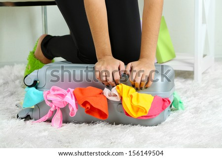 Suitcase with clothes on carpet on room background - stock photo