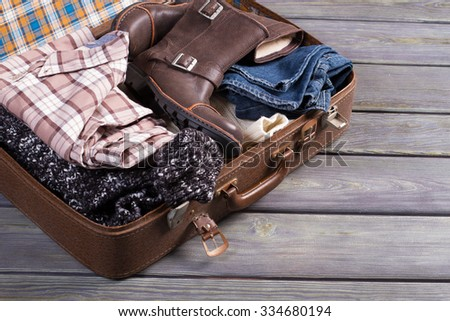 Suitcase with clothes. Retro suitcase full of things. - stock photo