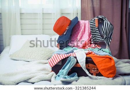 Suitcase with clothing on bed in room - stock photo