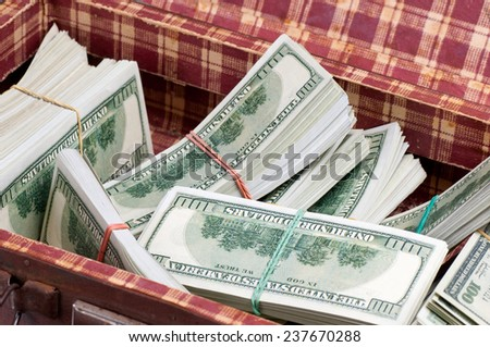 Suitcase with one hundred dollars banknotes. - stock photo