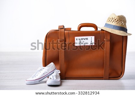 Suitcase with stickers on floor in room - stock photo