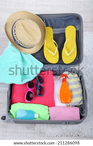 Suitcase with things on white carpet on the floor for traveling somewhere close to water for spending summer vacation