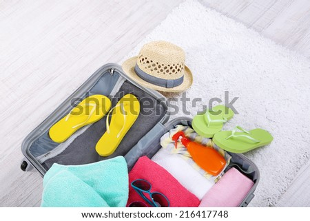 Suitcase with things on white carpet on the floor for travelling somewhere close to water for spending summer vacation - stock photo
