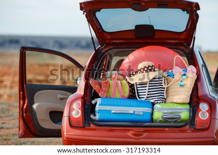 Suitcases and bags in trunk of car ready to depart for holidays. Moving boxes and suitcases in trunk of car, outdoors. trip, travel, sea. car on the beach with sea on background - stock photo