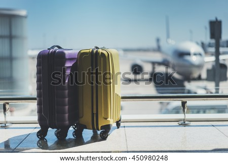 Suitcases in airport departure lounge, airplane in background, summer vacation concept, traveler suitcases in airport terminal waiting area, empty hall interior with large windows, focus on suitcases - stock photo