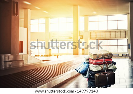 Suitcases on a cart at the airport arrival terminal - stock photo