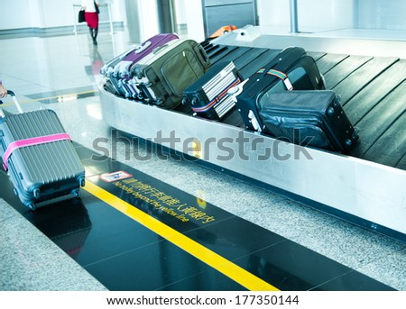 suitcases on conveyor belt of airport. - stock photo