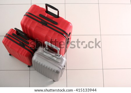 Suitcases on tile background - stock photo