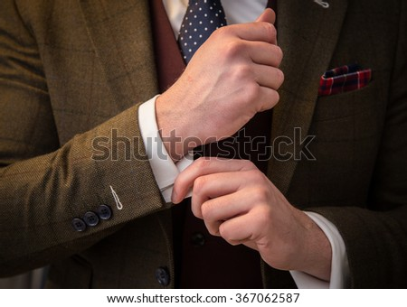 Suited man fixing cufflinks