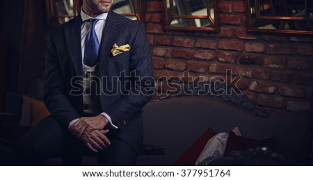 Suited man posing in a bar - stock photo
