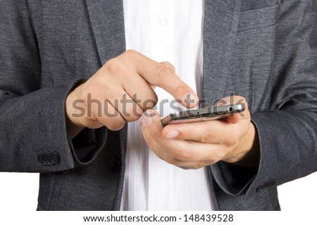 suited man using a touch screen phone with his finger