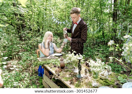 Suited young man  serving the tea to yong girl at funny table in forest.