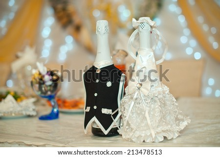 Suits of the groom and the bride on bottles with champagne.