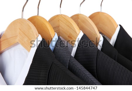 Suits with shirts on hangers on light background