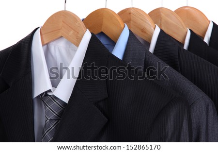 Suits with shirts on hangers on white background - stock photo