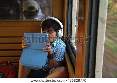Sukhothai, Thailand-April 18, 2016;Asian boy traveling by train listening to music and playing games on tablet.
