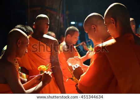 SUKHOTHAI, THAILAND - May 6, 2016: Thai Buddhist monks meditate with candle lighting during the religious ceremony to ASALHA PIJA Day on May 6, 2016 at WAT KLONG TA KIAN in SUKHOTHAI,Thailand. - stock photo