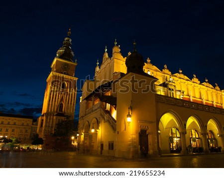 Sukiennice and Town Hall Tower in Krakow by night, Poland - stock photo