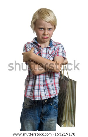 Sulking child holding a gift bag isolated on white background - stock photo