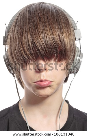 sulking cute teenager boy with hair over his eyes and headphones. - stock photo