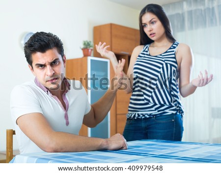 Sulking young man and longhaired girl blaming each other during home quarrel  - stock photo