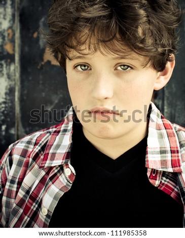 Sullen boy looking into camera - stock photo