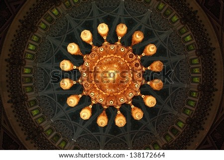 Sultan Qaboos Grand Mosque in Muscat: Details of ornate chandelier and arabesque design dome and ceiling. - stock photo