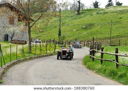 SULZANO, ITALY - APRIL 12: A black MG TA, a Lancia Aprilia and a BMW328 take part to the Franciacorta Historic classic car race on April 12, 2014 in Sulzano. The car were built in 1936, 1937 and 1938. - stock photo