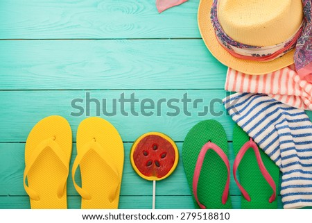 Summer accessories and candy on blue wooden background. Selective focus - stock photo