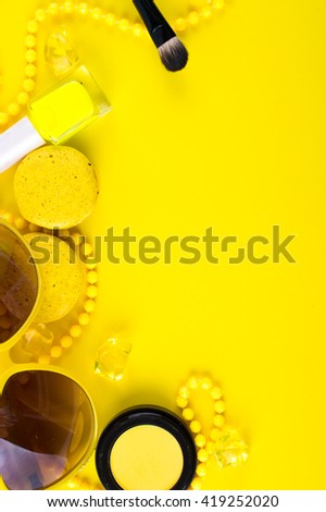 Summer accessories and cosmetics for relaxation on a yellow background - sunglasses, lipstick, powder, colored beads, nail polish. View from above. Flat lay. - stock photo
