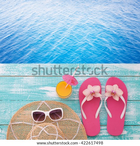 Summer accessories on boards near the sea. Flip-flops on beach. Tropical flower orchid. Flat mock up for design. Top view.