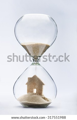 Summer accommodation concept with falling sand taking the shape of a house - stock photo