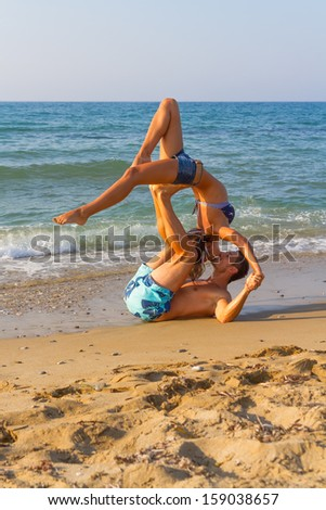 Summer afternoon at a sandy beach with the ocean in the background, a young couple practices a dance scene.