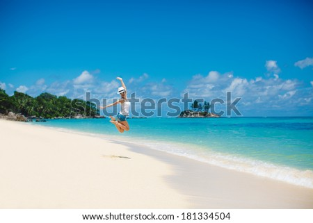 summer and holiday concept - laughing woman jumping on the beach - stock photo