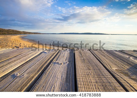 Summer At The Beach. Wooden dock overlooks a sunny sandy beach with a blue water horizon. - stock photo