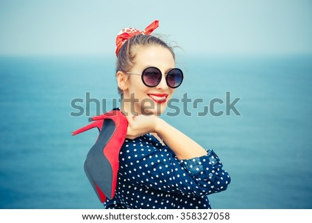 Summer at the sea. Close up portrait beautiful happy free young pretty woman stylish fashion girl looking at you, camera smiling holding red shoes isolated seascape ocean background,  outdoor vacation - stock photo