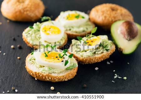 Summer avocado sandwich on bagel with boiled eggs and fresh thyme on stone black background, selective focus