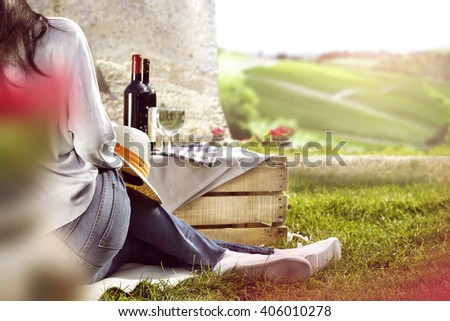 summer background of blurred flowers and woman body white shoes and wine on box