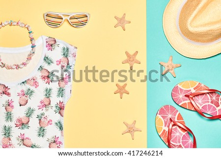 Summer background. Summer girl clothes set, accessories. Fashion summer  T-shirt, stylish hat, necklace and trendy hipster sunglasses. Unusual modern. Overhead, top view on yellow blue - stock photo