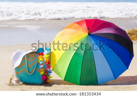 Summer background with rainbow umbrella, white hat and bag on the sandy beach