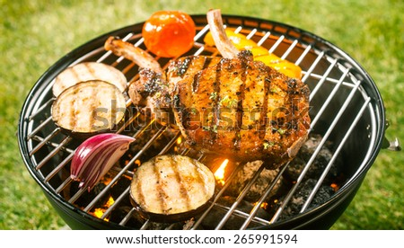 Summer barbecue with pork cutlets and fresh healthy vegetables grilling over the hot coals outdoors on the green grass in the garden - stock photo