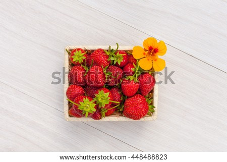 ... Set with berries in bowl with orange flower. Top view fruit flat lay